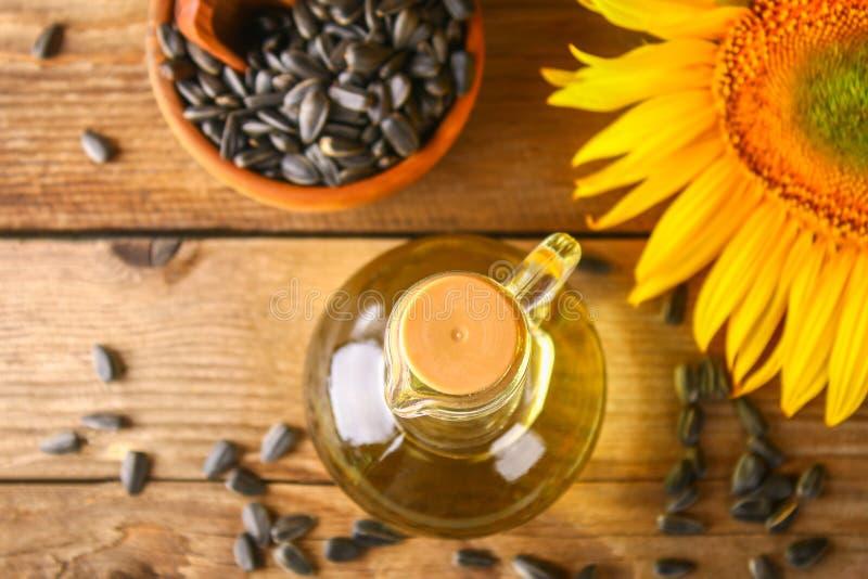 向日葵油和向日葵种子在小大袋在传统土气木背景 有机和eco食物概念 健康foo 免版税库存照片