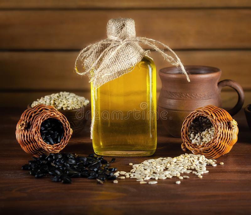 向日葵油和向日葵种子在木背景 免版税库存照片