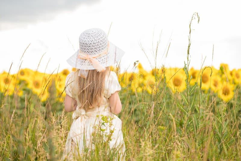 向日葵的婴孩 一件白色礼服和一个白色帽子的女孩在一个领域用向日葵 免版税图库摄影