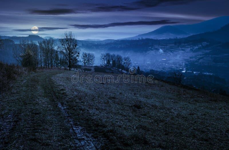 向村庄的土路在小山下在晚上 免版税库存图片