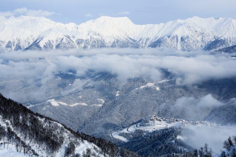 向用雪和云彩和高山的路盖的滑雪胜地旅馆在索契 免版税图库摄影