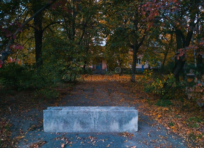 向被放弃的大厦的封锁的路秋天晚上 库存照片