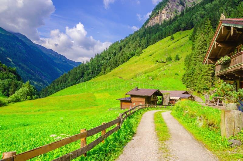 向高山房子的乡下公路在阿尔卑斯,奥地利 库存图片