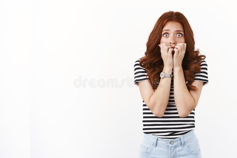 吓得吓呆了、羞怯怯、胆怯、缺乏安全感、穿着条纹T恤、咬指甲、盯着相机的可爱红发女人 免版税库存图片
