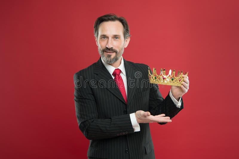 君主制的衣服举行金黄冠标志的人有胡子的人 成为的国王仪式 奖和成就 ?? 免版税库存图片
