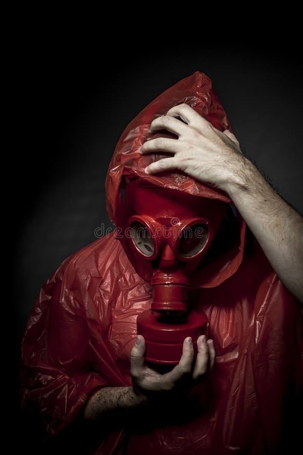 含毒物,一个防毒面具的A人在烟。黑背景和 库存图片