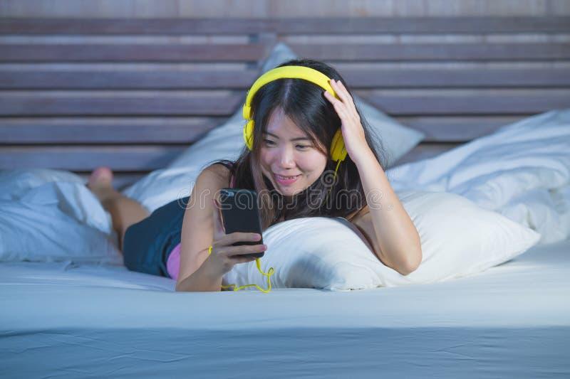 听与在床relaxe的耳机耳机和手机的音乐歌曲的年轻甜和愉快的亚裔中国人20s妇女 免版税库存照片