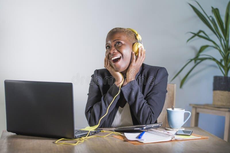 听与耳机的音乐被激发和快乐工作的年轻愉快的黑人美国黑人的妇女在便携式计算机书桌在mod 免版税库存照片