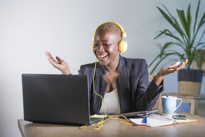 听与耳机的音乐被激发和快乐工作的年轻愉快的黑人美国黑人的妇女在便携式计算机书桌在mod 图库摄影