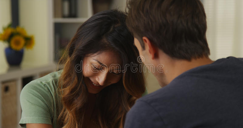 听人种间的夫妇在家谈话和 库存照片