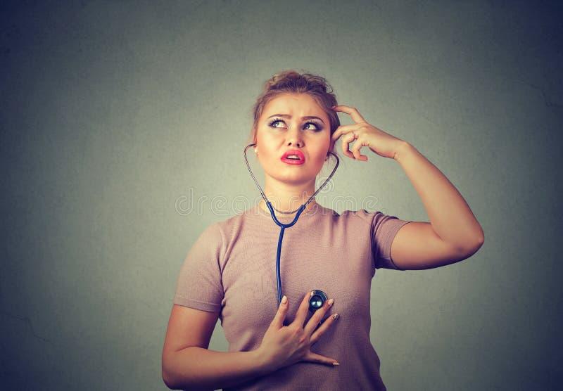 听体贴的妇女她的与听诊器的心脏 免版税图库摄影
