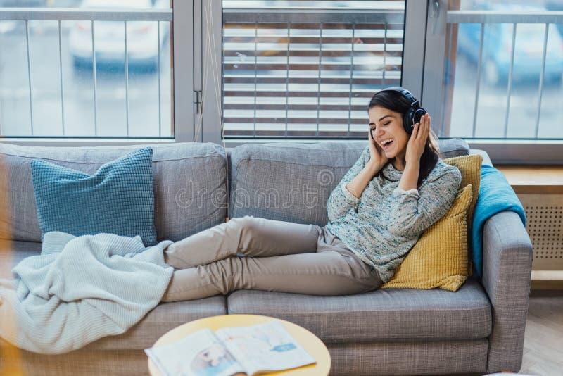 听到与大耳机和唱歌的音乐的快乐的妇女 享受听到音乐,音乐疗法 放松与音乐, 免版税库存图片