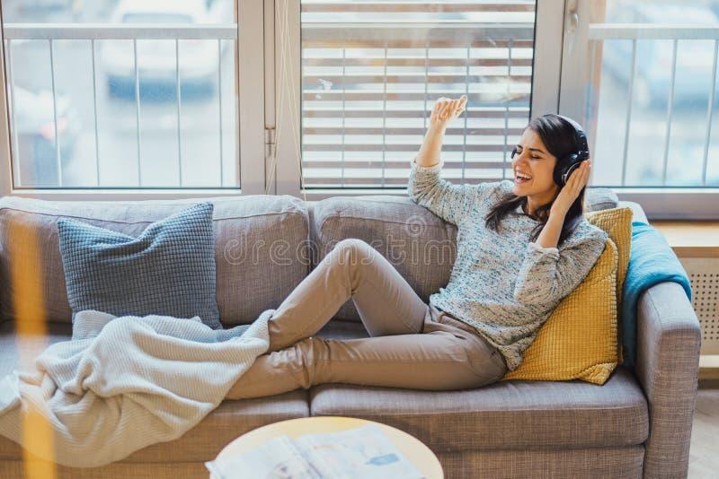 听到与大耳机和唱歌的音乐的快乐的妇女 享受在家听到音乐及时时间 免版税库存照片