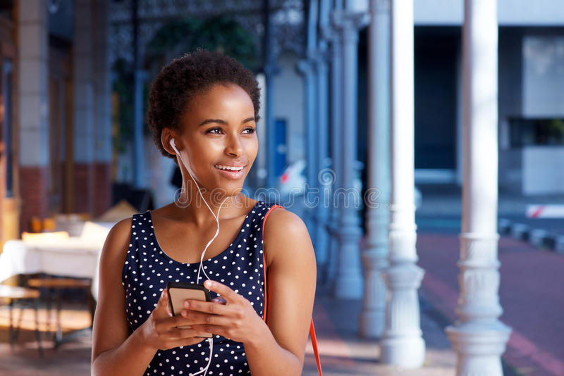 听到与巧妙的电话的音乐的典雅的年轻黑人妇女 免版税库存照片