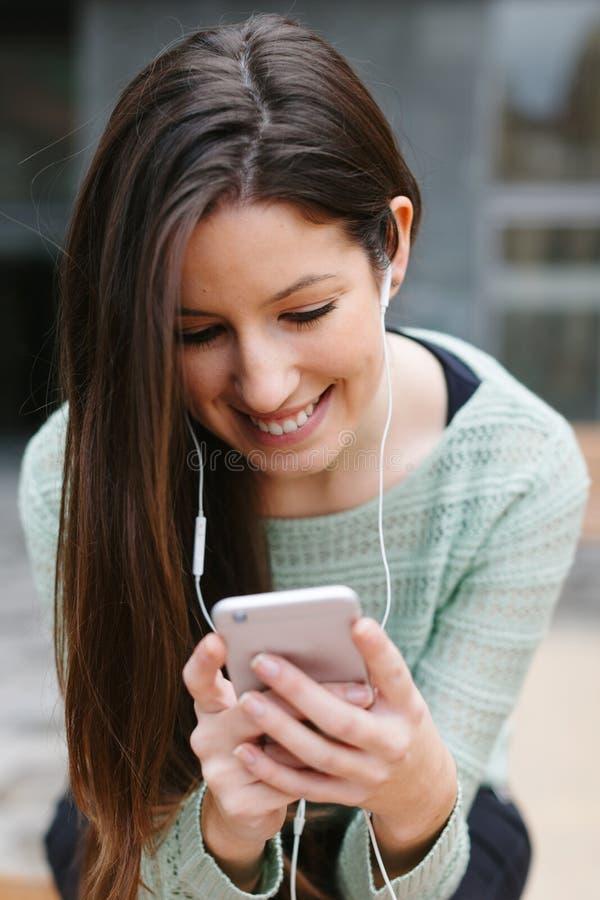 听到与电话的音乐的一名年轻美丽的妇女的特写镜头户外 免版税库存照片