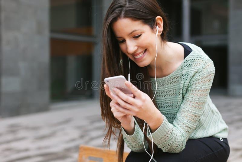 听到与电话的音乐的年轻美丽的妇女户外 免版税图库摄影