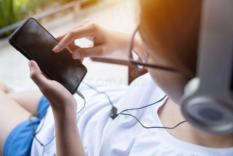 听到与耳机和巧妙的电话的音乐的妇女 免版税库存图片