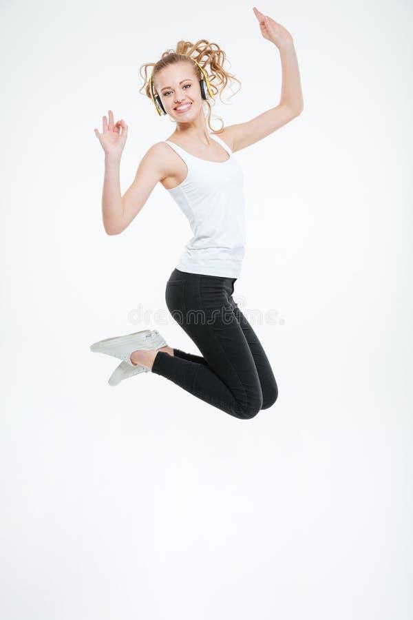 听到与耳机和跳跃的音乐的快乐的少妇 库存图片