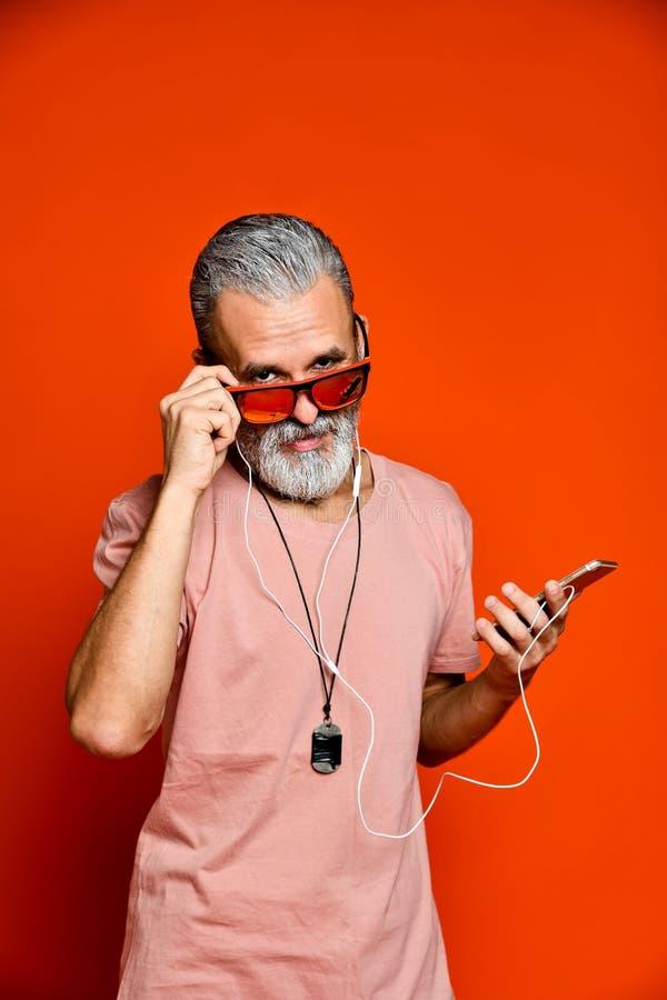 听到与耳机的音乐的一个年长人的图象 免版税库存图片