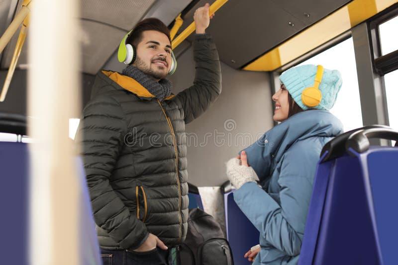 听到与耳机的音乐的人们在公共交通工具 免版税库存图片