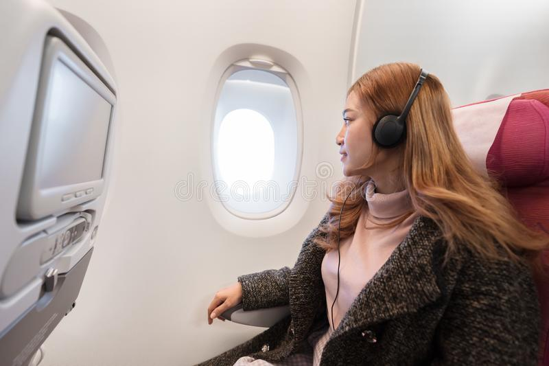 听到与耳机的音乐的妇女在飞机在飞行中计时 库存图片