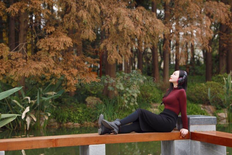 听到与耳机的音乐的年轻亚裔中国妇女坐在树下 免版税库存照片