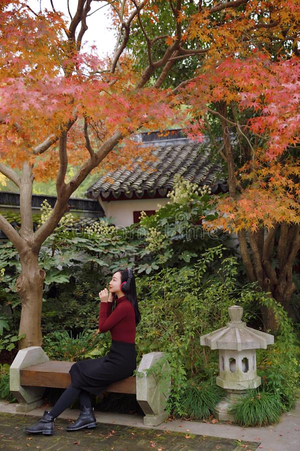 听到与耳机的音乐的年轻亚裔中国妇女坐在树下 免版税库存图片