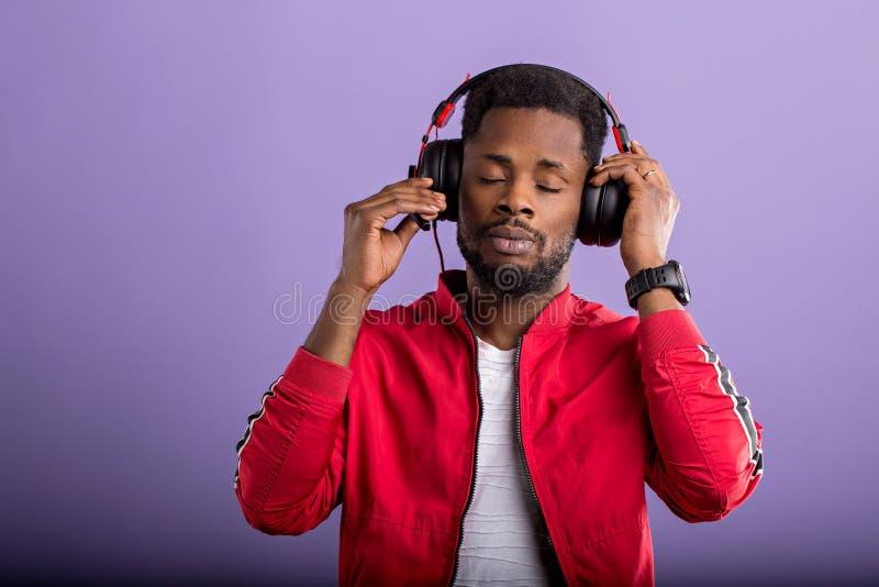 听到与耳机的音乐的年轻非洲人画象  库存照片