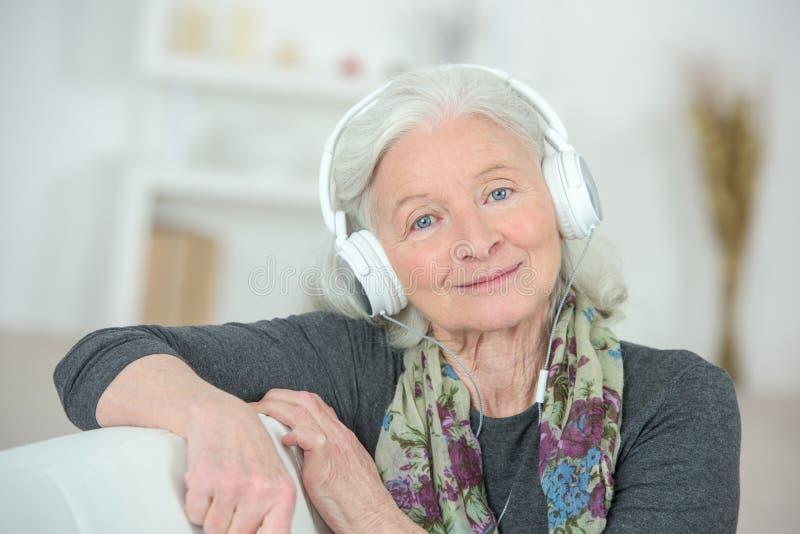 听到与耳机的音乐的年长妇女 免版税库存图片