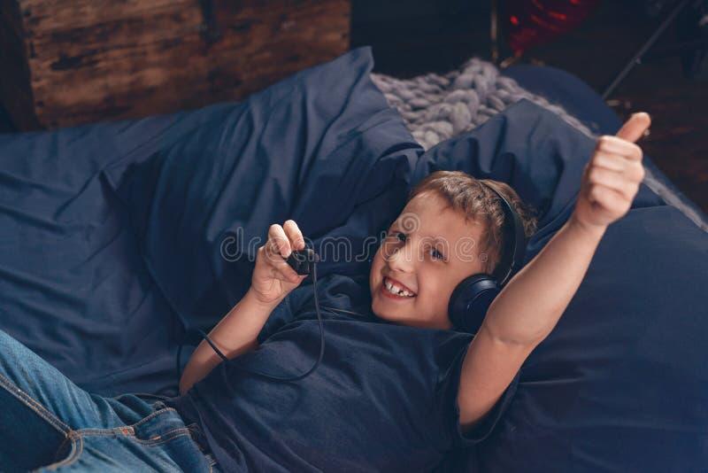 听到与耳机的音乐的微笑的男孩,在床上 图库摄影