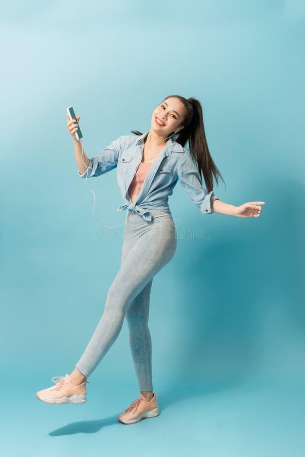 听到与耳机的音乐的快乐的少女,当跳过和唱歌蓝色背景时 库存照片