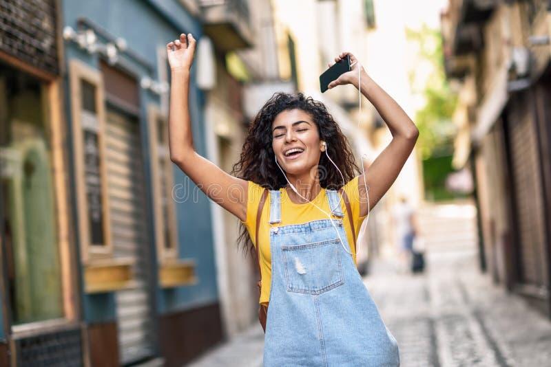 听到与耳机的音乐的滑稽的妇女户外 便衣的阿拉伯女孩有卷曲发型的在都市背景中 图库摄影