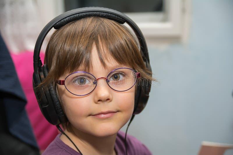 听到与耳机的音乐的美丽的女孩 库存照片