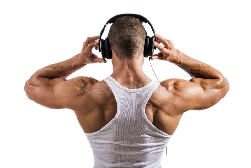 听到与耳机的音乐的肌肉爱好健美者 免版税图库摄影