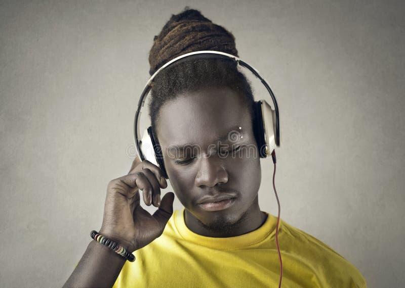 听到与耳机的音乐的非洲人 库存照片