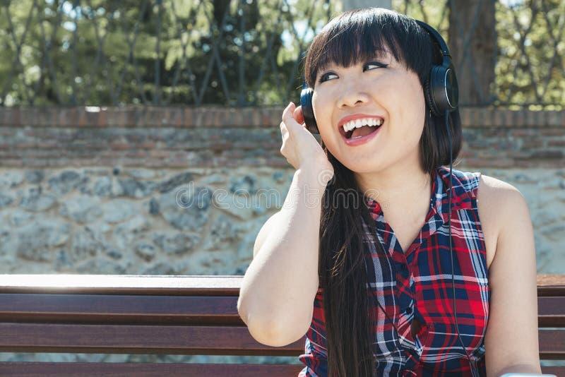 听到与headph的音乐的年轻可爱的女孩画象  库存照片