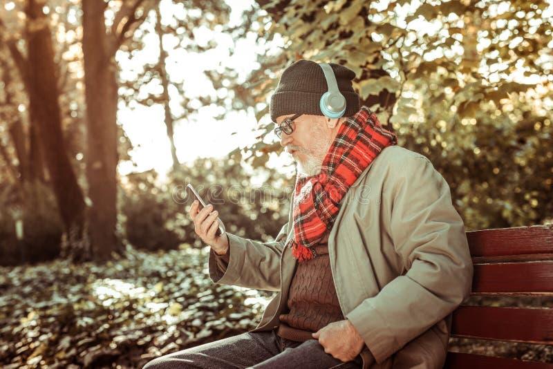 听到从他的智能手机的音乐的严肃的人 免版税图库摄影