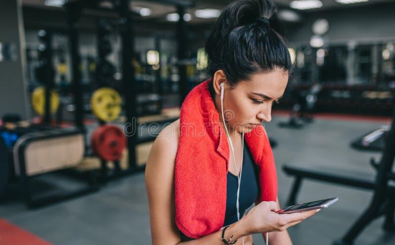 听到从她的智能手机的音乐的一美丽的运动的年轻女人的画象,为在健身房的一种坚硬锻炼做准备 人们 库存照片