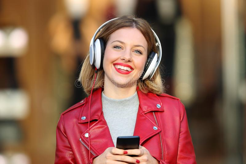 听到从看您的电话的音乐的时尚女孩 库存图片