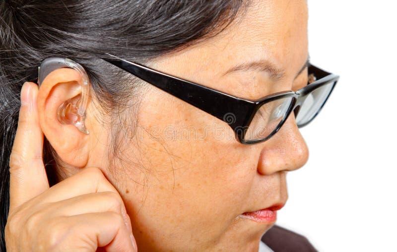 听到佩带的妇女的帮助镜片 免版税库存图片