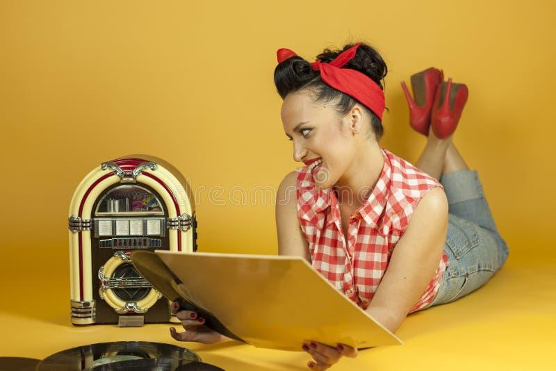 听到在一台老自动电唱机r的音乐的画象美丽的别针 库存图片
