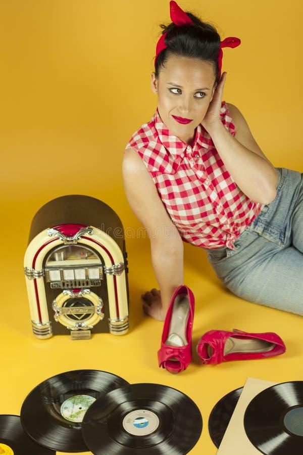 听到在一台老自动电唱机r的音乐的画象美丽的别针 免版税图库摄影