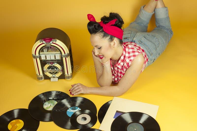 听到在一台老自动电唱机r的音乐的画象美丽的别针 库存照片
