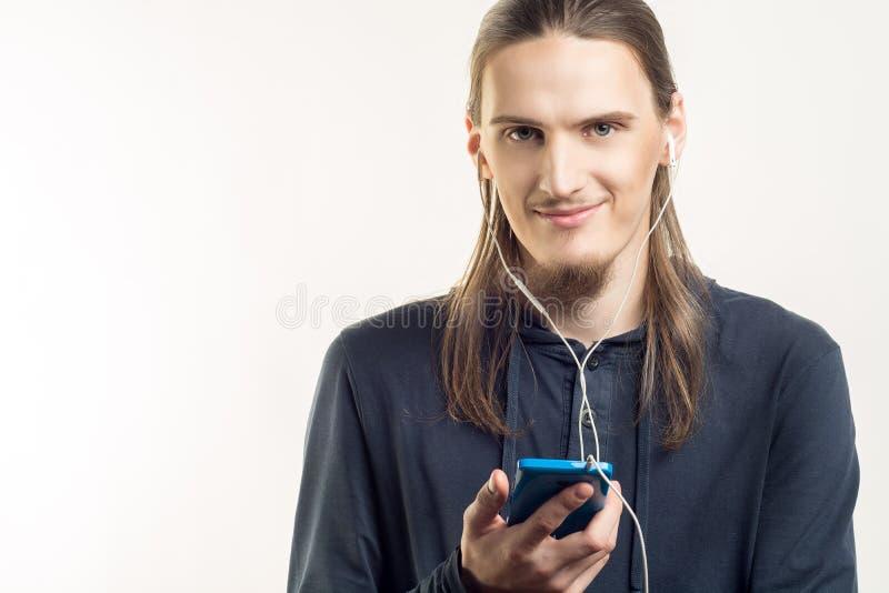 听到在他的智能手机的音乐和看在白色背景的照相机的英俊的微笑的年轻人 库存照片