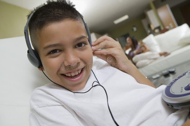 听到在便携式的光盘播放机的音乐的男孩客厅画象关闭的  库存图片