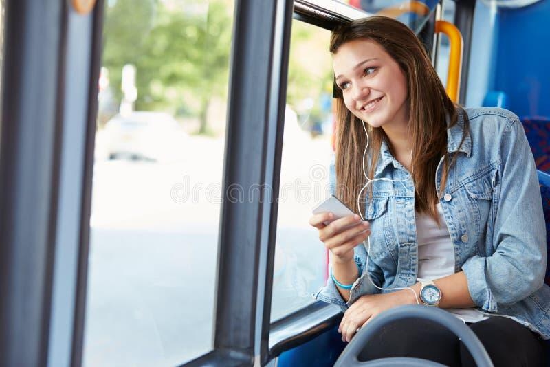 听到在公共汽车的音乐的十几岁的女孩佩带的耳机 库存图片