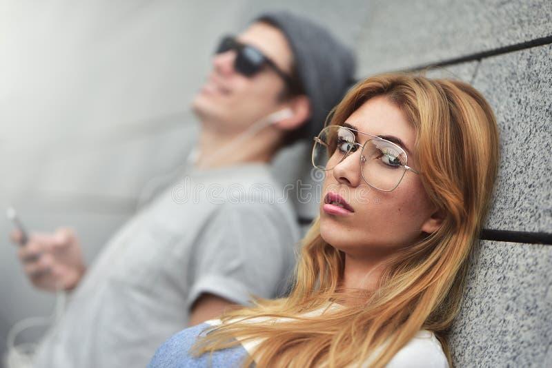 听到在同一个对的音乐的年轻有吸引力的夫妇耳机,穿戴在时髦的衣裳反对a背景  免版税库存照片