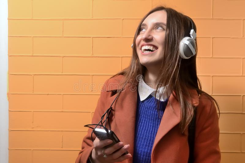 听到在大耳机的音乐的女孩 库存照片