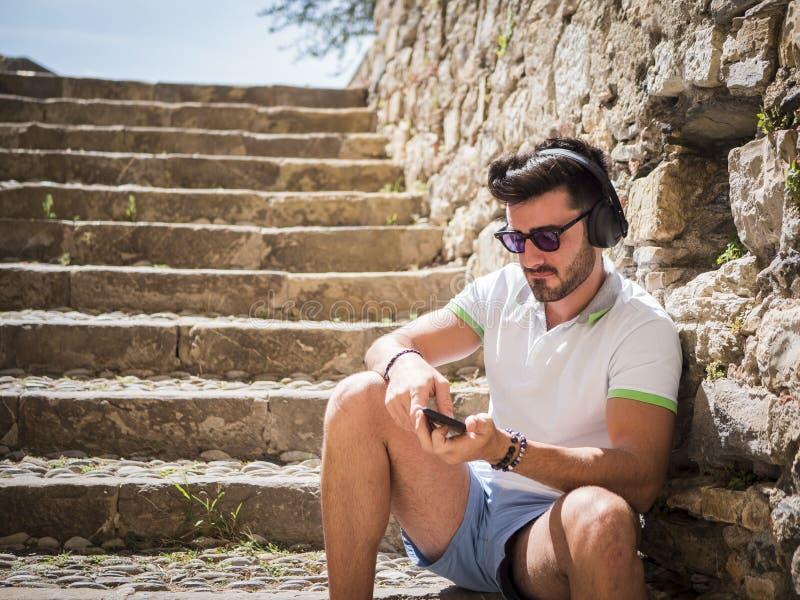 听到在室外的耳机的音乐的帅哥 库存照片
