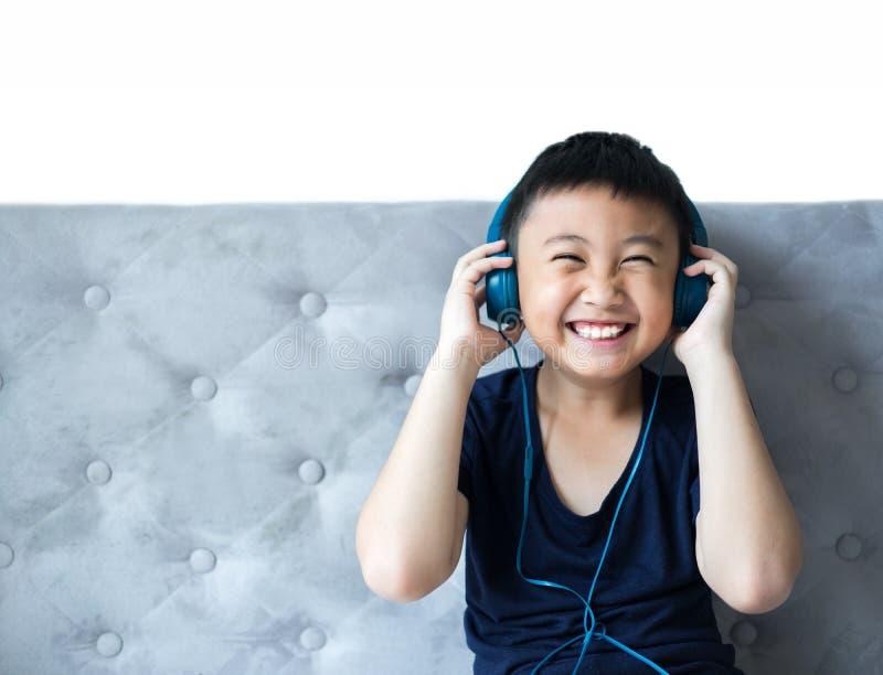 听到在床上的音乐的小男孩在卧室为放松 图库摄影